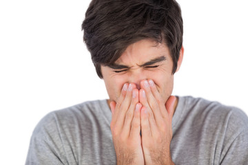 Young man sneezing