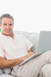 Smiling man on his couch using laptop looking at camera