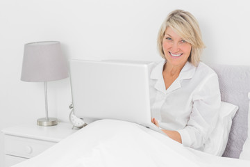 Happy woman sitting in bed with laptop looking at camera