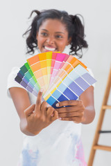 Excited woman showing colour charts and pointing