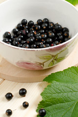 Black currants in a bowl on a wooden table