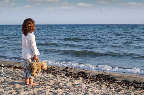 little girl with teddy bear standing on beach and looking at the