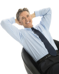 Portrait Of Happy Businessman Relaxing On Office Chair