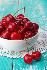 Bowl of fresh red cherries on blue wooden background