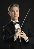 Music Conductor Smiling While Directing With His Baton