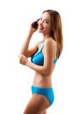 attraktive junge Frau im Bikini beim telefonieren