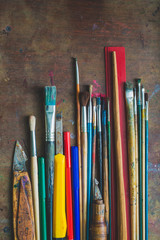 Set of paint brushes and office supplies on the table