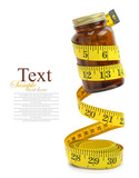 Measuring tape with a bottle of diet pills