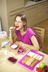 Happy beautiful woman having breakfast eating strawberry