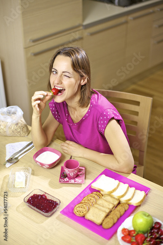 Happy beautiful woman having breakfast eating strawberry
