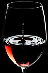 Rotwein tropft in ein Rotweinglas