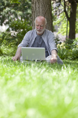 modern male pensioner on computer under a tree