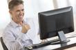 Happy Businessman Looking At Computer Monitor