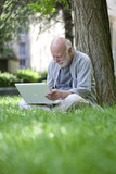 studious retired man working outdoors in green environment