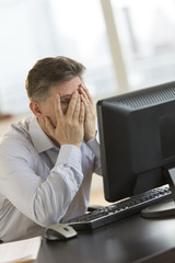 Frustrated Businessman With Hands On Face Looking At Computer