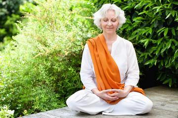 Seniorin meditiert im sommerlichen Garten