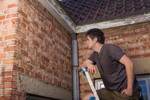 Young man inspecting the wall of an old house