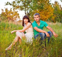 Portrait of young romantic couple sitting in forest enjoying