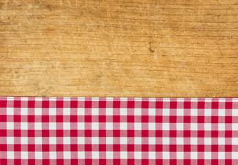 Rustikaler Holzhintergrund mit einem rot karierten Tischtuch