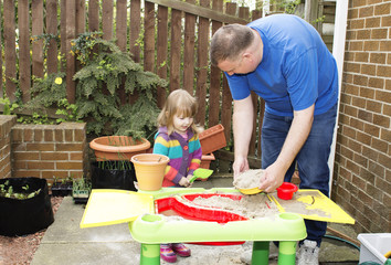 Father and daughter playing at a sand table
