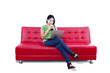 Asian female relaxing on red sofa - isolated