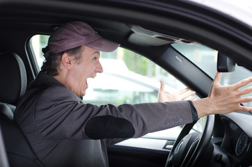 Angry upset man at wheel driving his car screaming