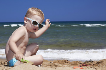 child plays on the beach in sand