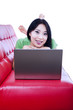 Happy female on red sofa with laptop - isolated