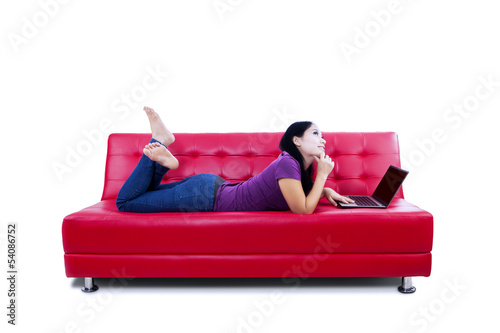 Thoughtful woman with laptop on couch