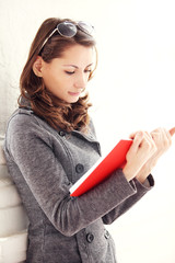 Image of young beautiful woman reading a book