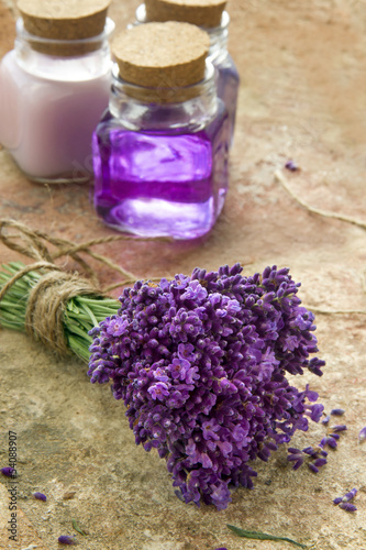 Bouquet of fresh purple flowers and bottles of soap and lotion