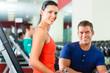 Trainer und Mann mit Hanteln im Fitness studio