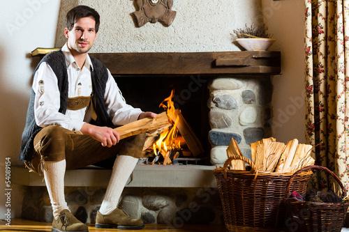 Junger Mann in Almhütte in den Alpen am Kamin