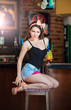 Attractive pinup woman in denim shorts sitting on bar stool