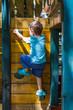 Little boy climbing on jungle gym