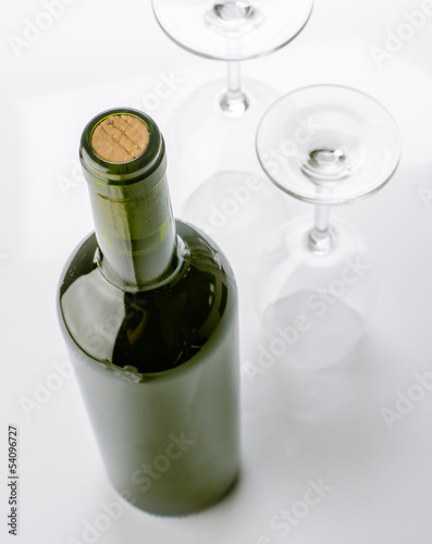 unopened wine bottle and empty glasses