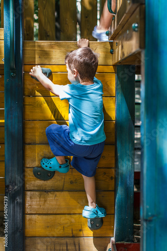Little boy climbing on jungle gym