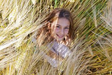 hübsches Mädchen sitzt im Kornfeld und schaut nach oben