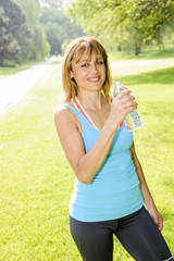 Happy woman drinking water while working out