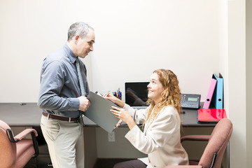 Coworkers reviewing document in office