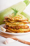 Green zucchini pancakes on a wooden board old
