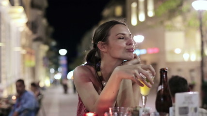 Beautiful woman drinking cocktail in outdoor bar, steadicam shot