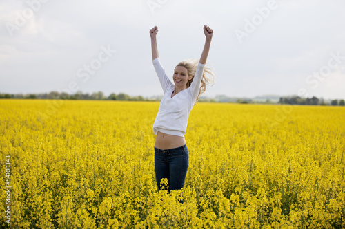 A young woman in a rape seed field jumping in the air