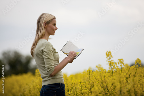 A young woman sketching a picture of a rape seed field in flower