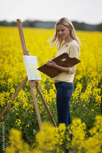 A young woman painting a picture of a rape seed field