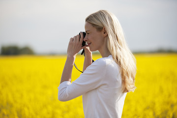 A young woman taking a photograph of a rape seed field