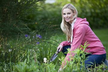 A young woman weeding a garden