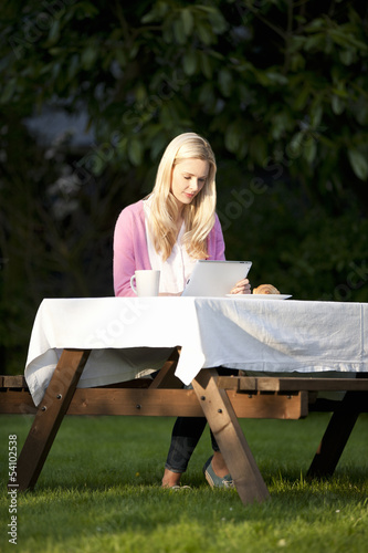 A young blond woman sitting in a garden using a digital tablet