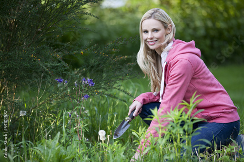 A young woman weeding a garden