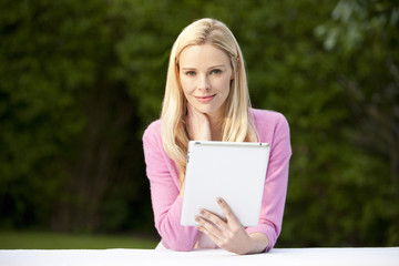 A young blond woman sitting in a garden holding a digital tablet